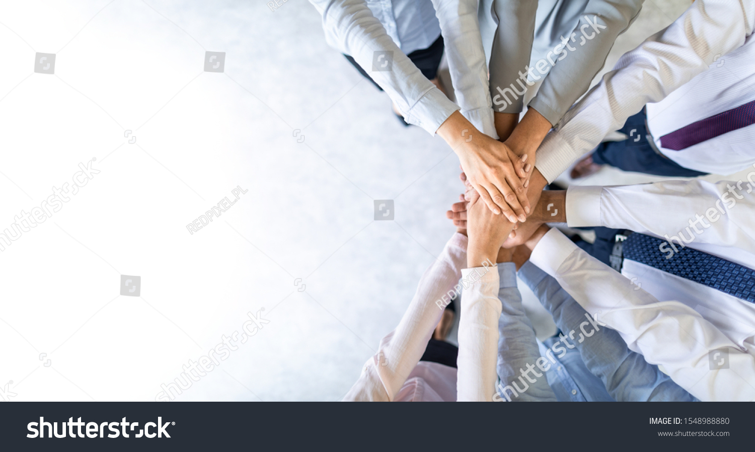 Close up top view of young business people putting their hands together. Stack of hands. Unity and teamwork concept. #1548988880