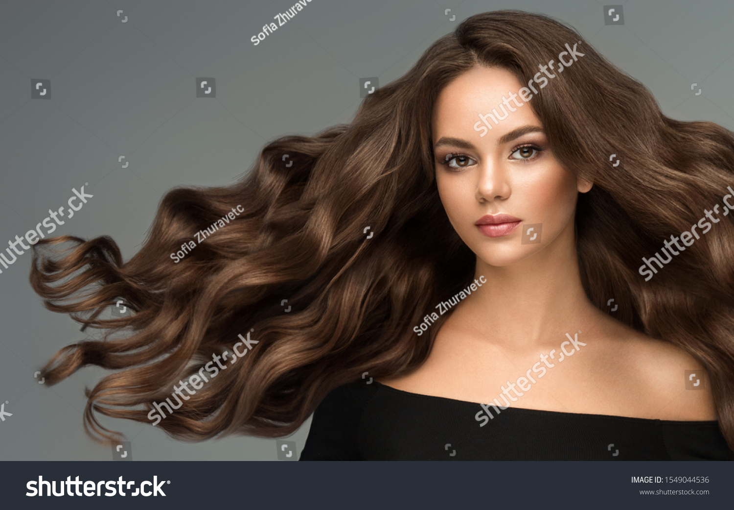 Beauty brunette girl with long  and   shiny wavy black hair .  Beautiful   woman model with curly hairstyle . #1549044536