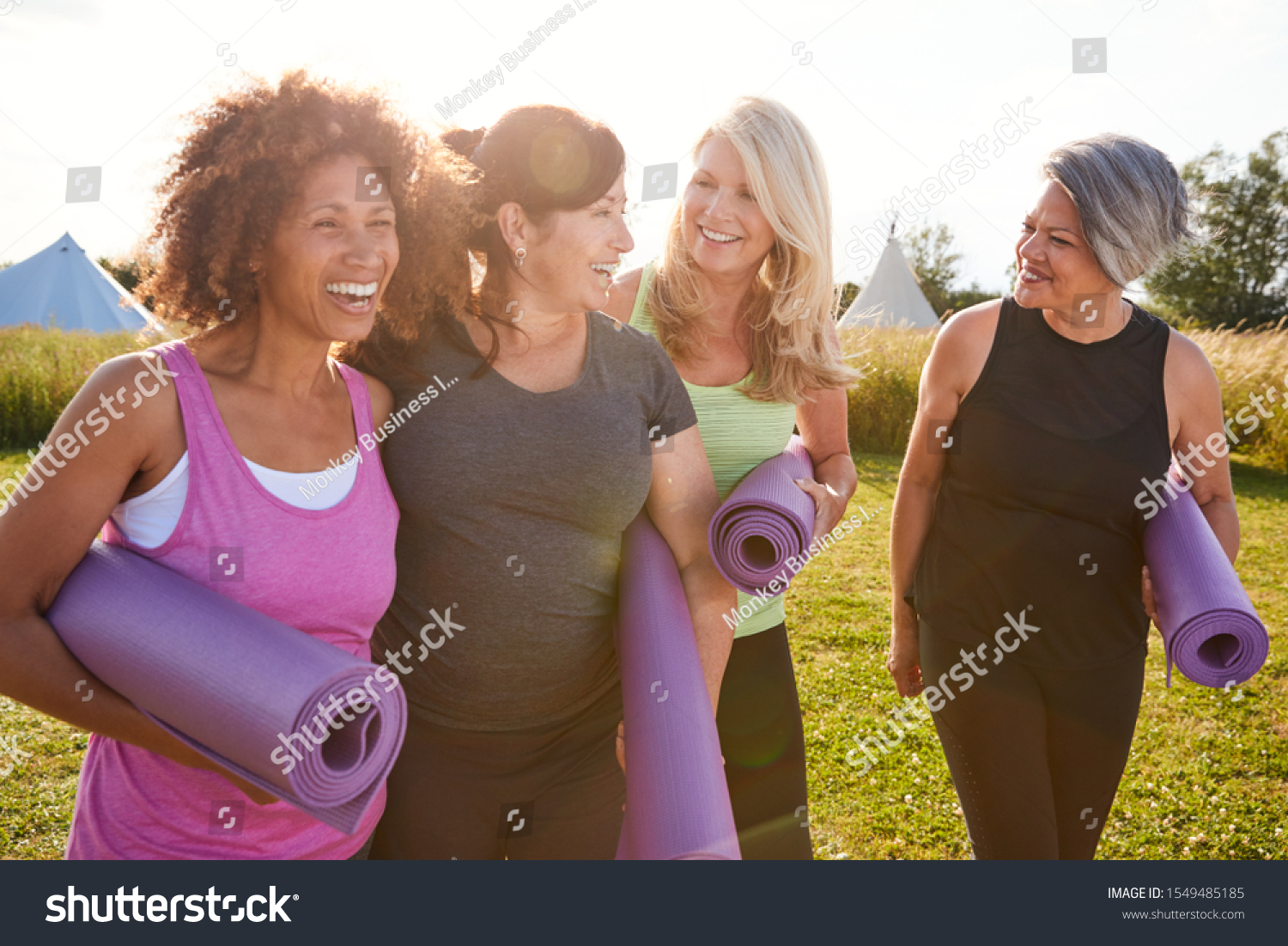 Group Of Mature Female Friends On Outdoor Yoga Retreat Walking Along Path Through Campsite #1549485185
