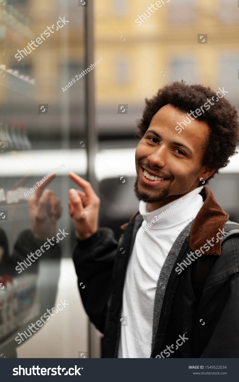 African man buys drink or sweets at vending machine outside. #1549522034