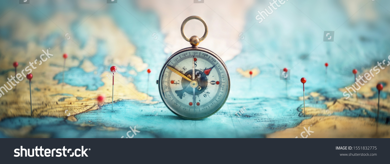 Magnetic compass  and location marking with a pin on routes on world map. Adventure, discovery, navigation, communication, logistics, geography, transport and travel theme concept background. #1551832775