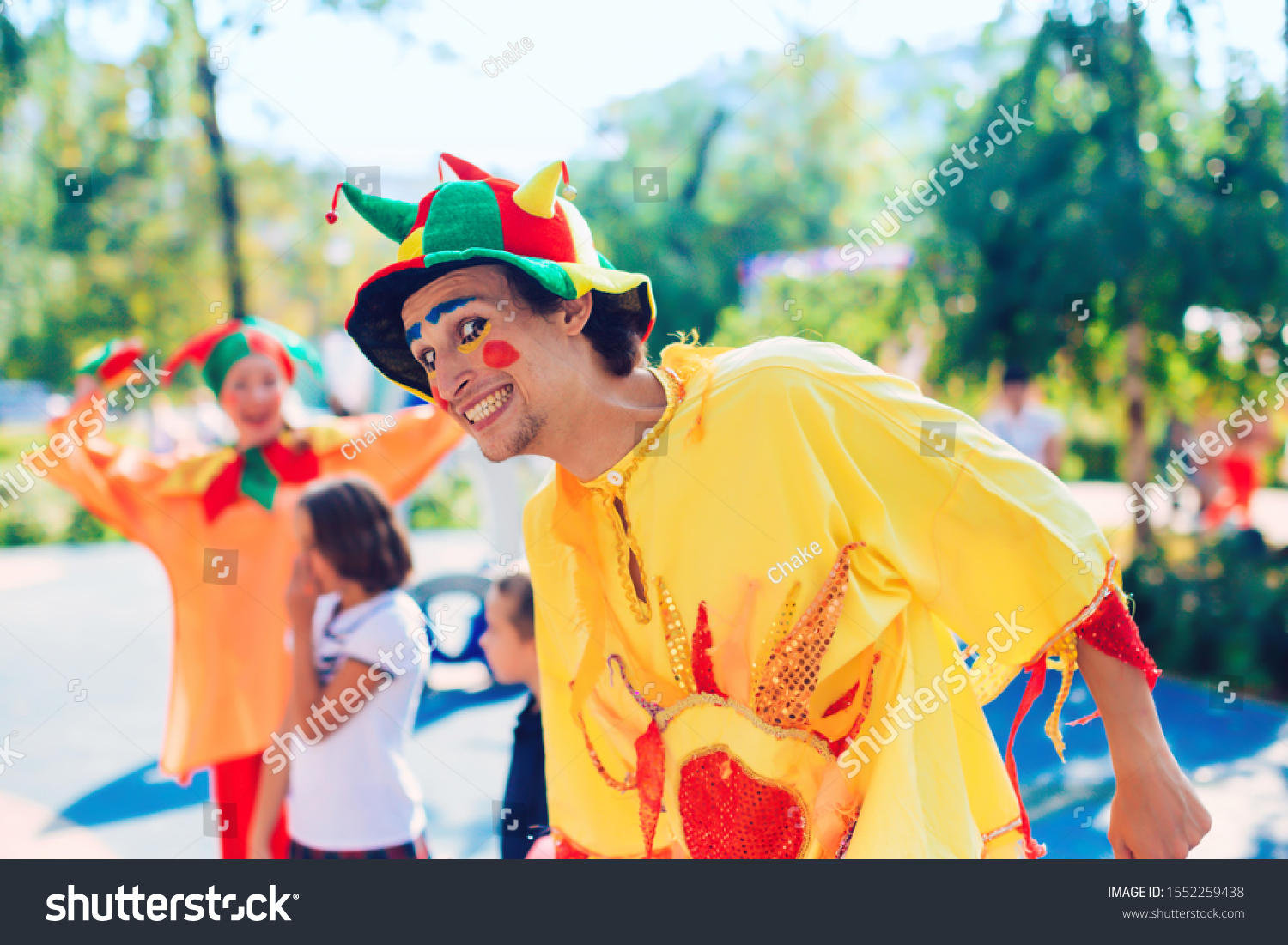Funny clown with a smile on his face in the process. Two clowns to entertain the children outdoors. One of the actors dressed #1552259438