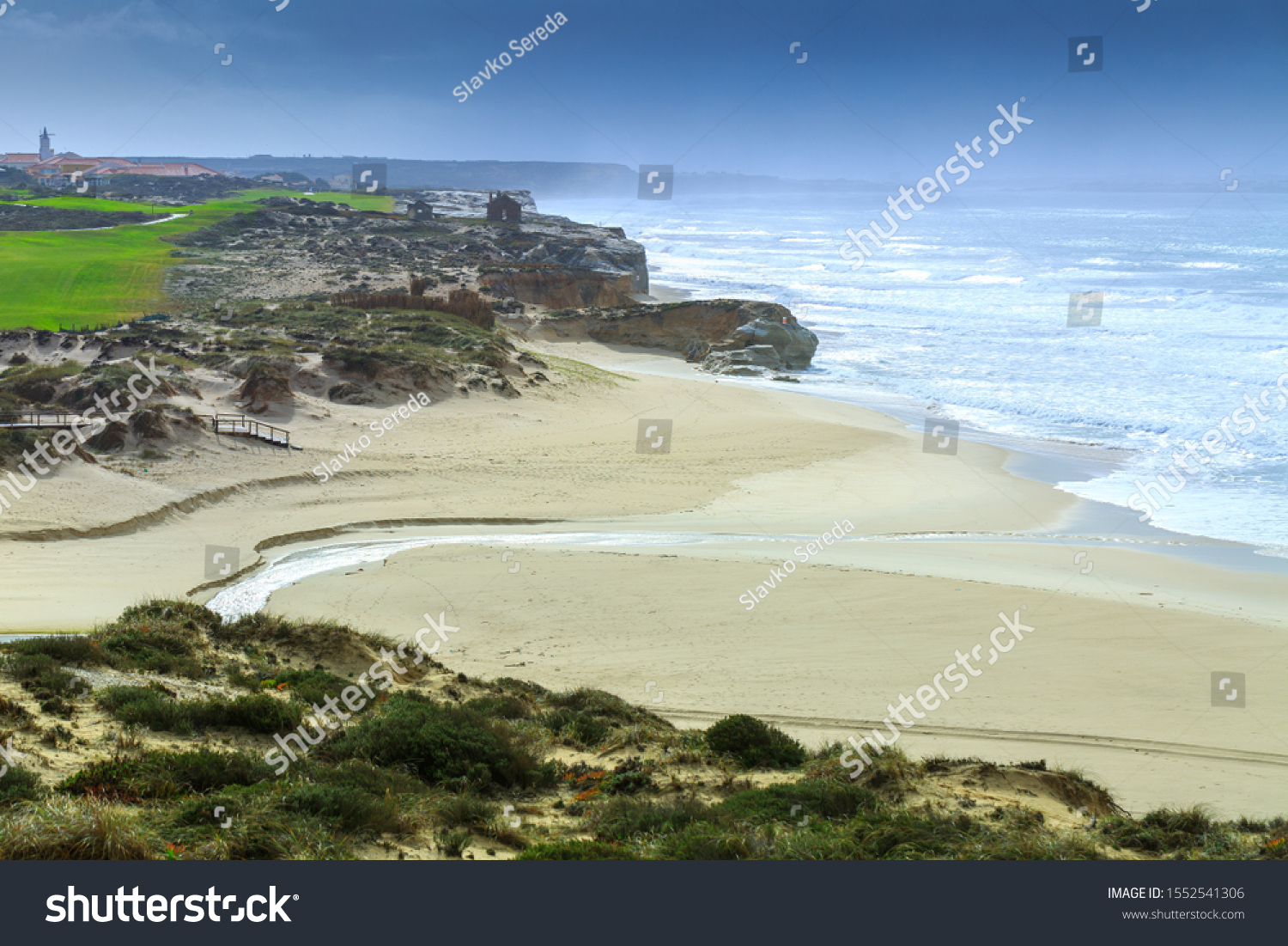 A ocean waves on the beautiful sand beach in at the cloudy stormy day. Breathtaking romantic seascape of ocean coastline. Praia d'el rey near Obidos Lagoon. Portugal. #1552541306