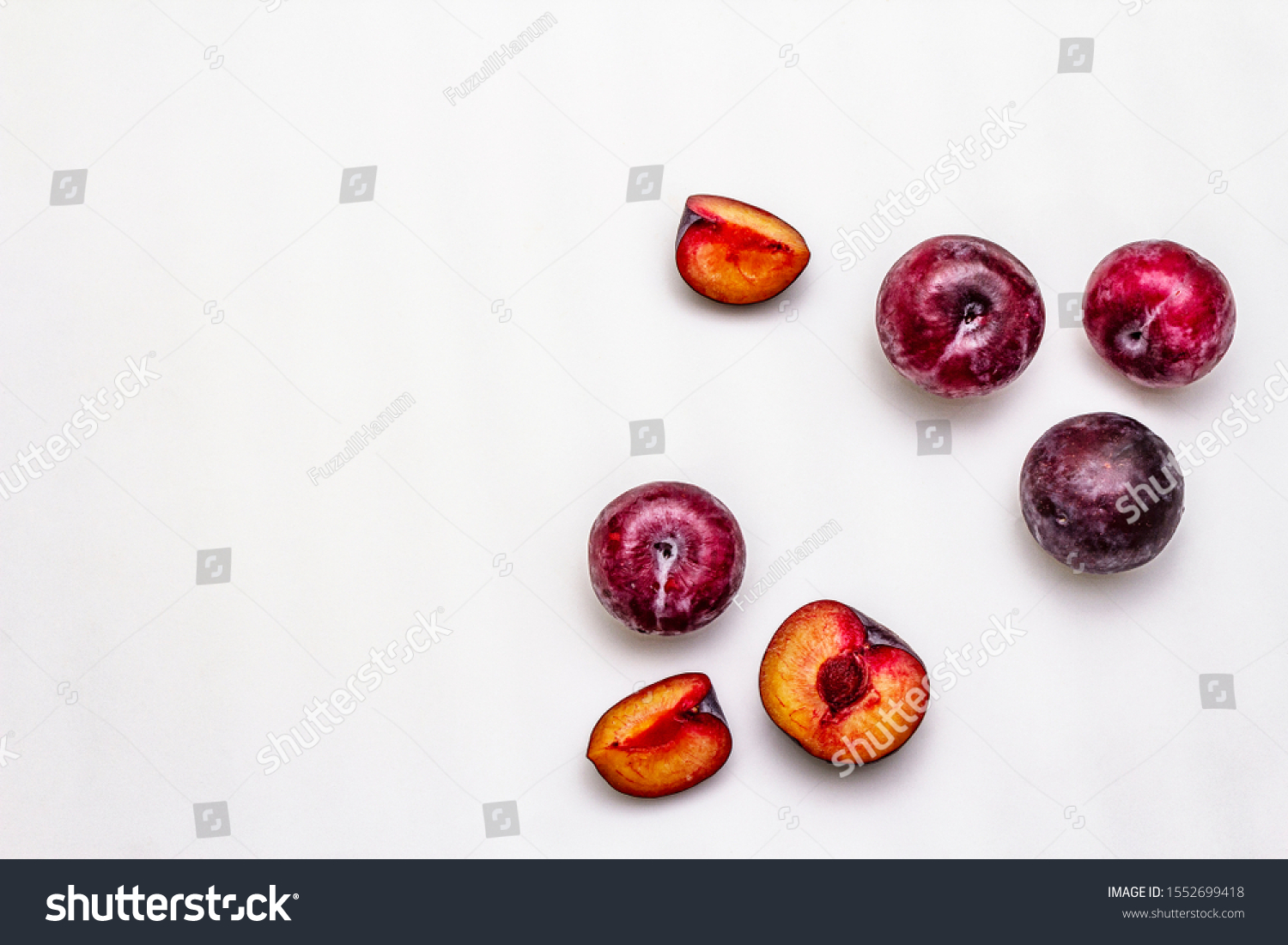 Ripe large purple plums. Fresh whole fruits, half sliced, seeds. Isolated on white background, copy space, top view #1552699418