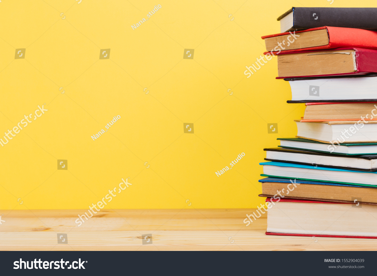 Simple Simple composition of many hardback books, unprocessed books on a wooden table and a yellow background. back to school. Copy space. Education. #1552904039