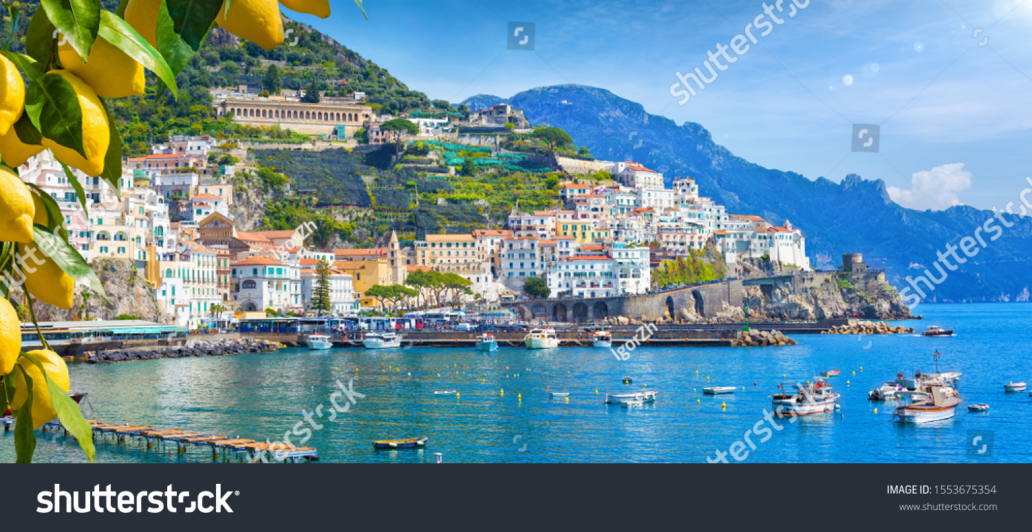 Panoramic view of beautiful Amalfi on hills leading down to coast, Campania, Italy. Amalfi coast is most popular travel and holiday destination in Europe. Ripe yellow lemons in foreground. #1553675354