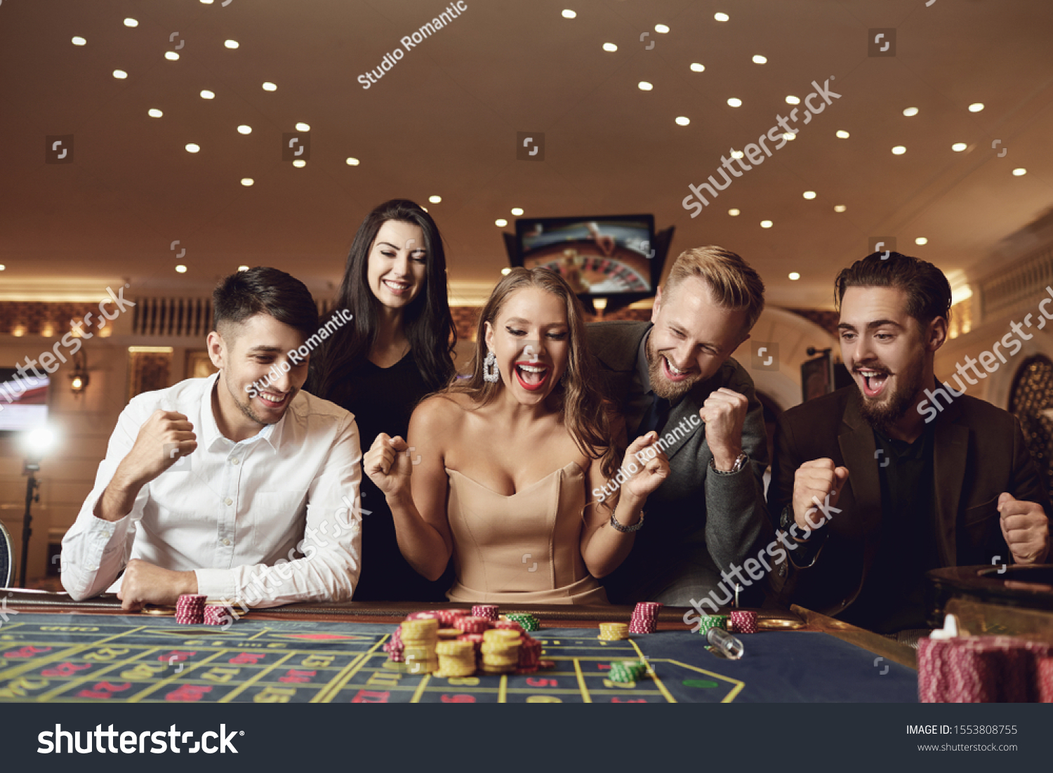 Happy people are betting in gambling at roulette poker in a casino #1553808755