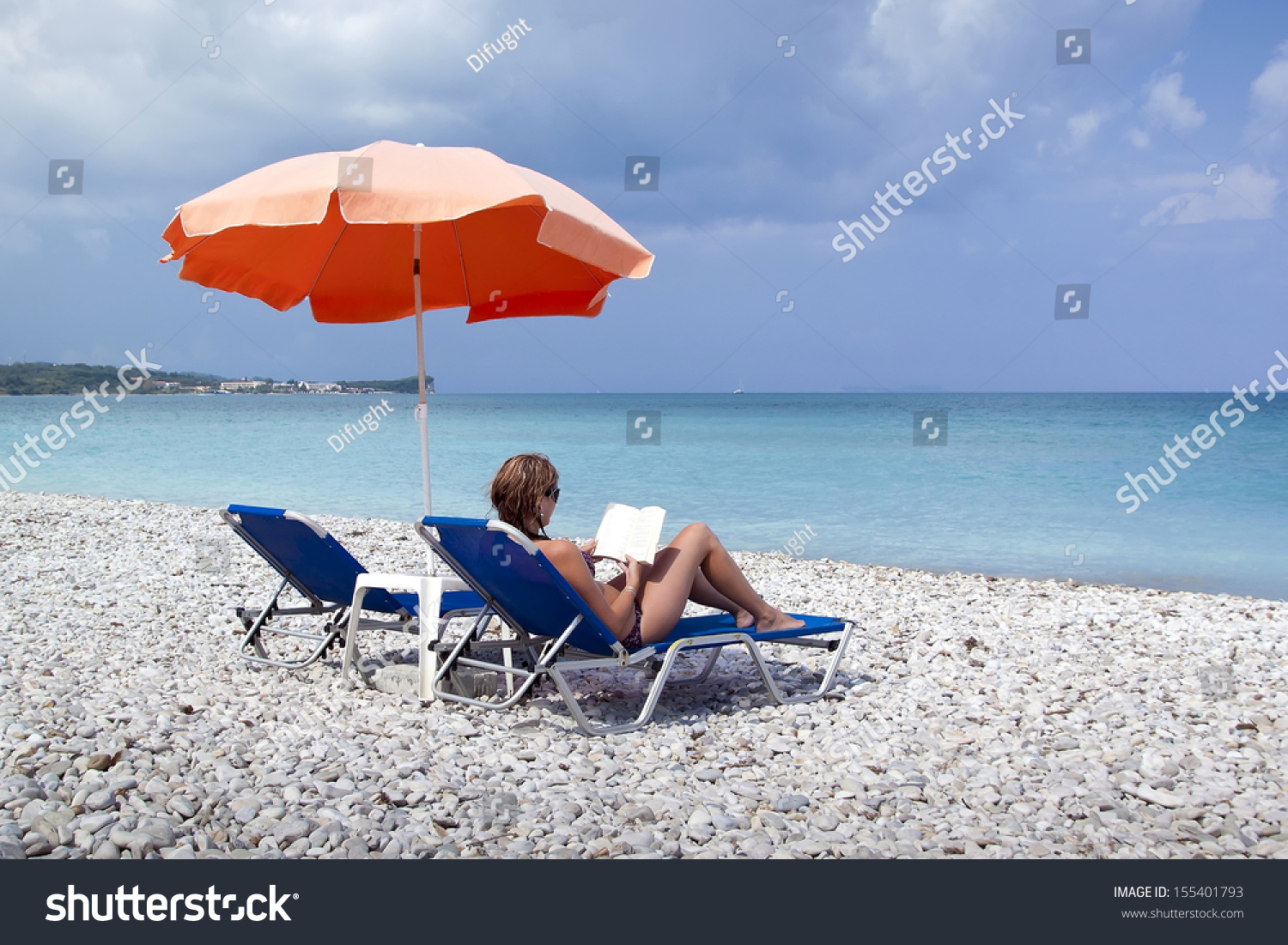 Sun Lounger And Umbrella On Empty Rock Beach With Reading ...