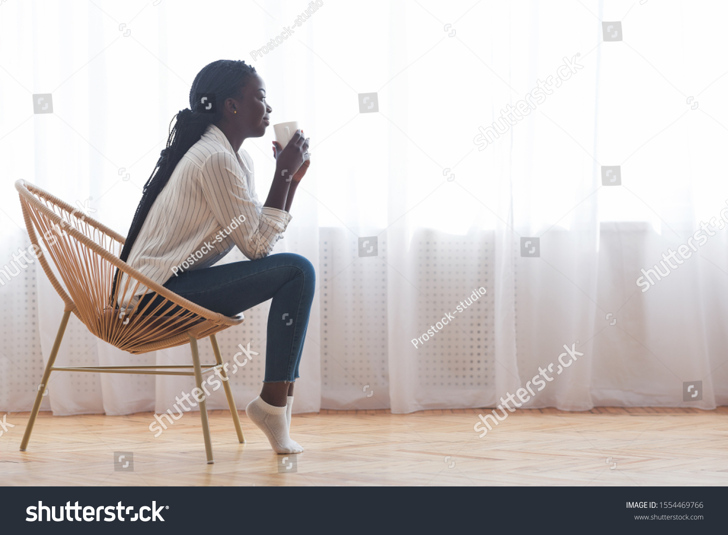 Time To Relax. African american girl sitting in wicker chair and drinking coffee against window at home, empty space #1554469766