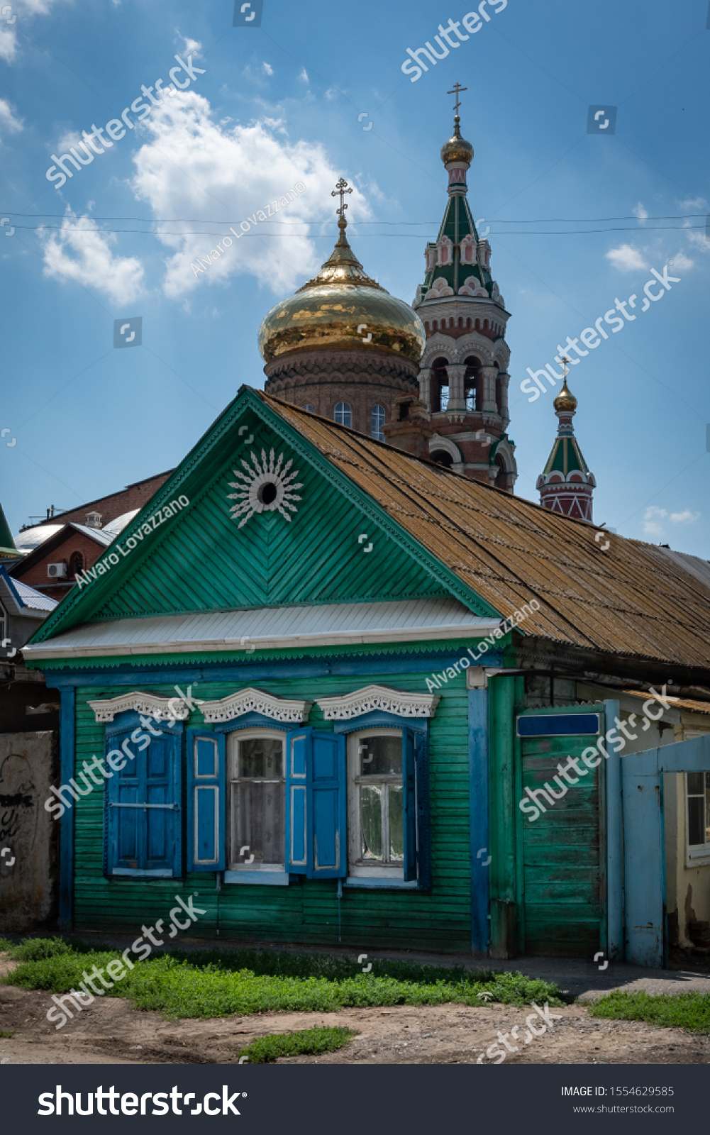 Traditional house in Astrakhan with an orthodox church in background, Russia