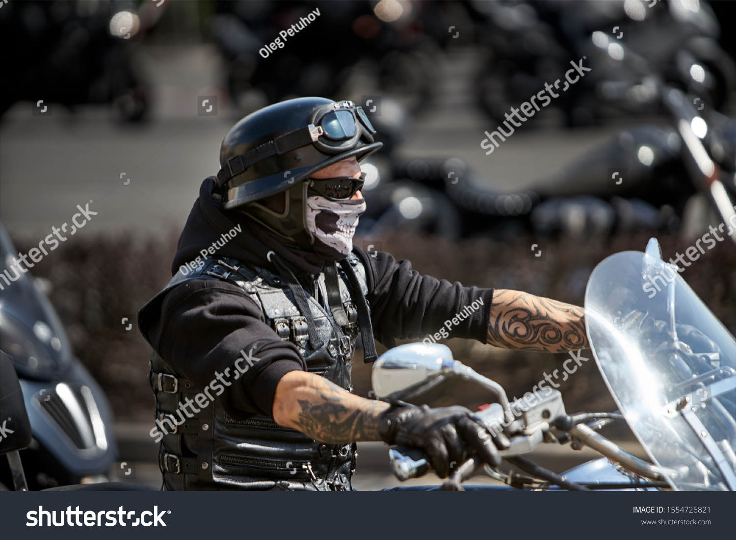Brutal biker with skeleton mask. unidentified motorcycle rider in a mask takes part in a motorcycle parade           #1554726821