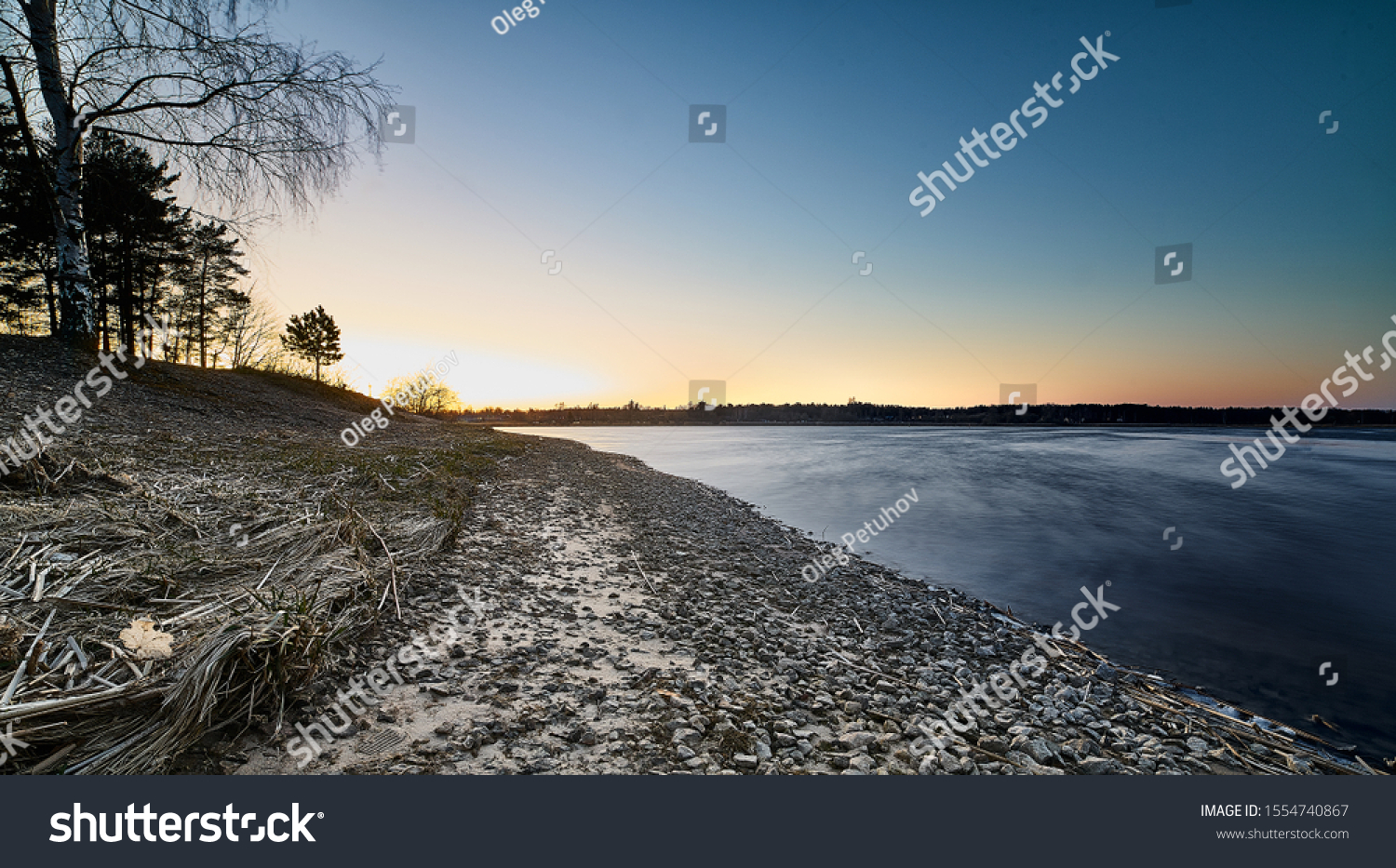 Sunset at the river coast. Smooth water at river #1554740867