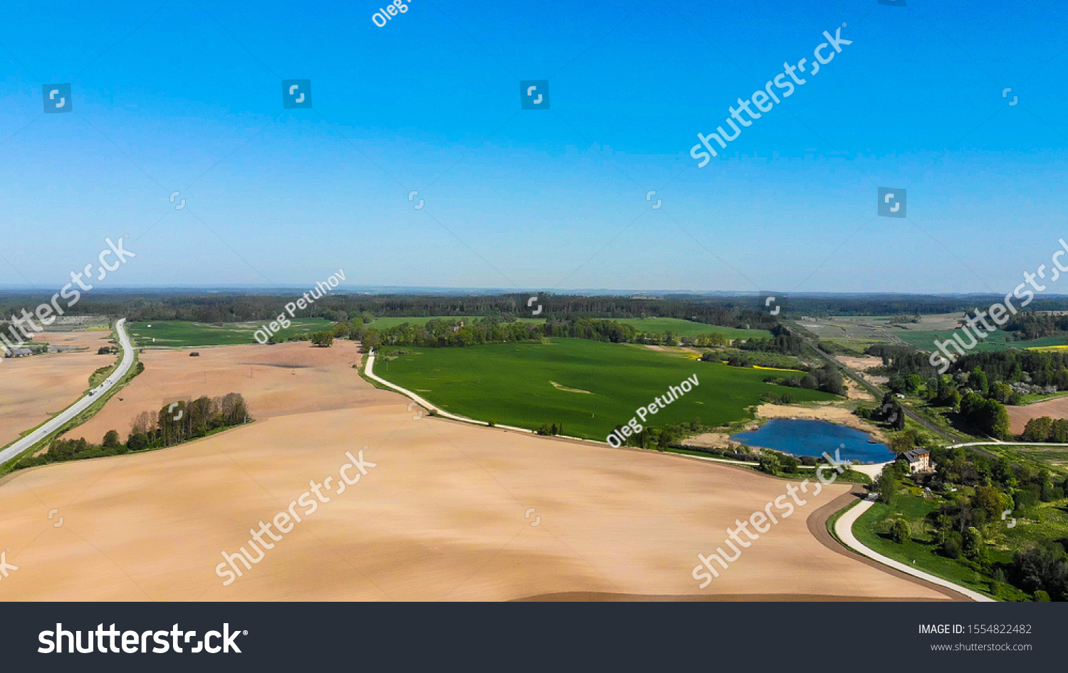 Farmers field. Green farmers field. shot from above, from drone. Field and forest. Beautiful top view of plowed and sown fields. Aerial panorama drone view of typical agricultural landscape. #1554822482