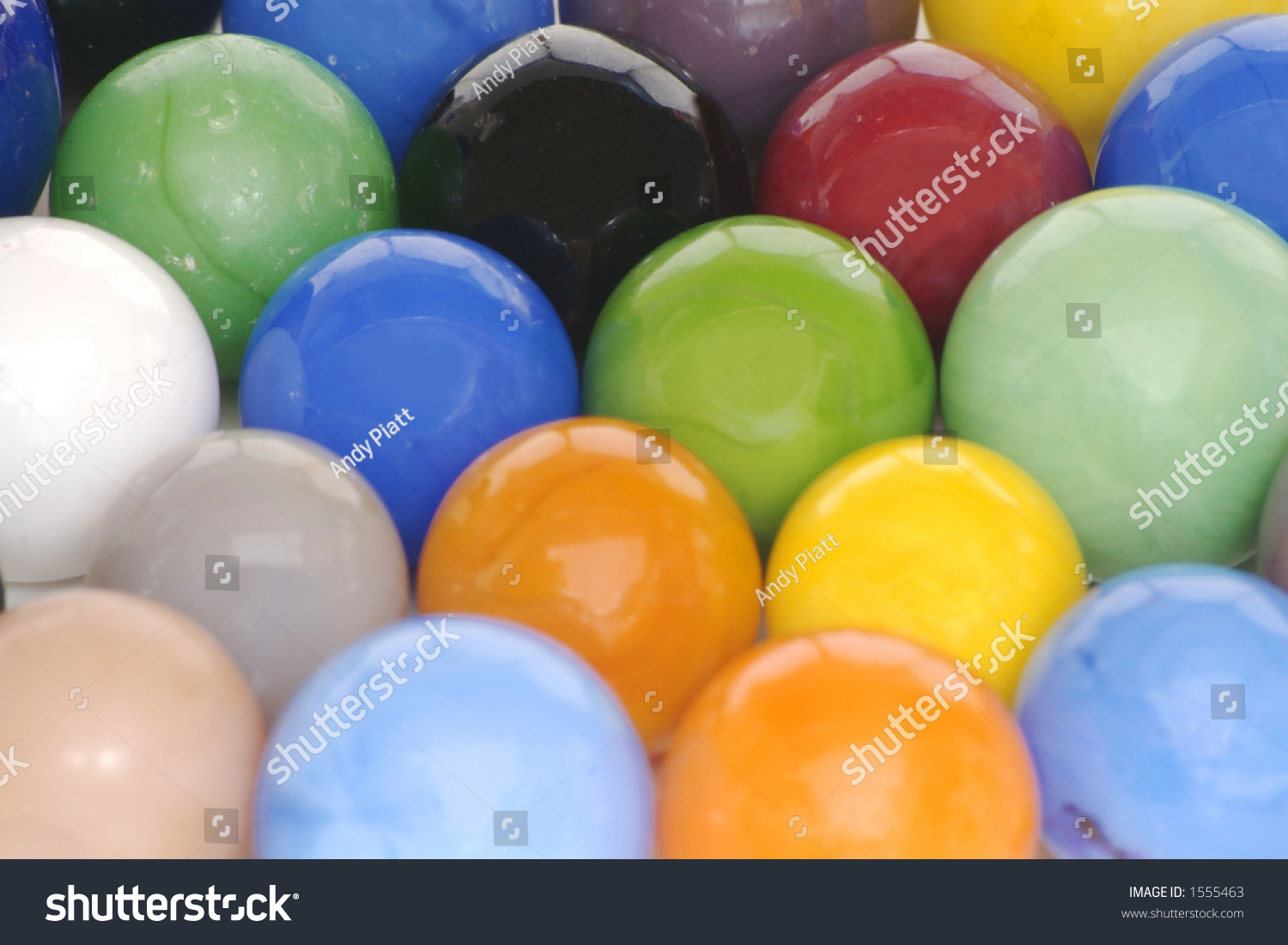 Solid White Toy Marbles : A solid background of brightly colored toy glass marbles