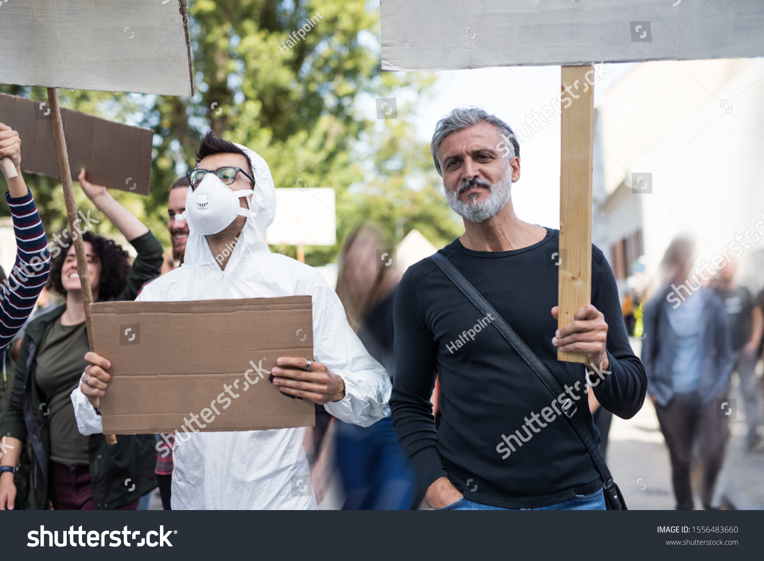 People with placards and protective suit on global strike for climate change. #1556483660
