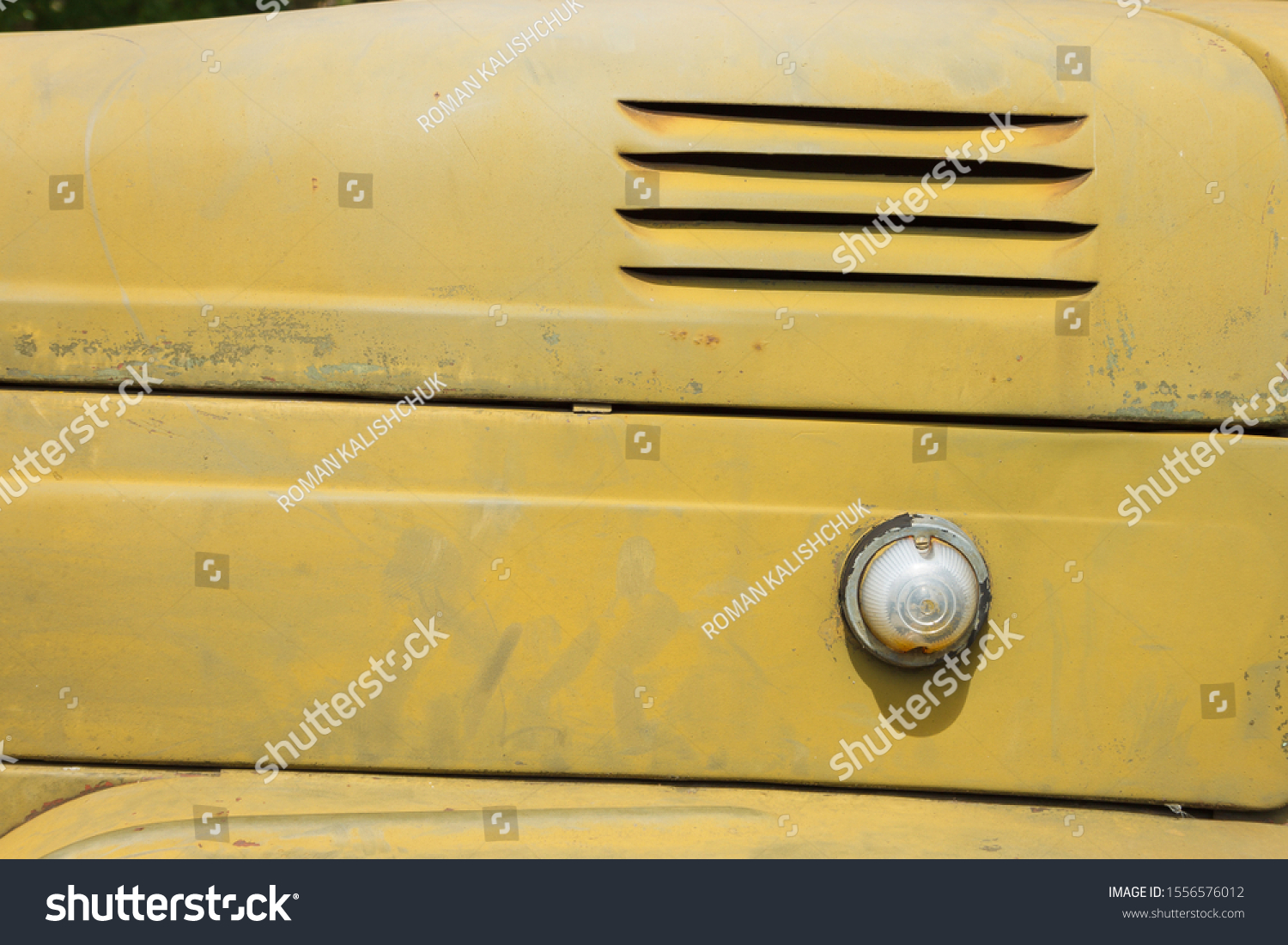 Details of the bonnet of a Soviet military truck. Side turn signal lights. Design elements and details of an old camouflage surface with exfoliated paint on a military truck. Car detail. Close-up #1556576012