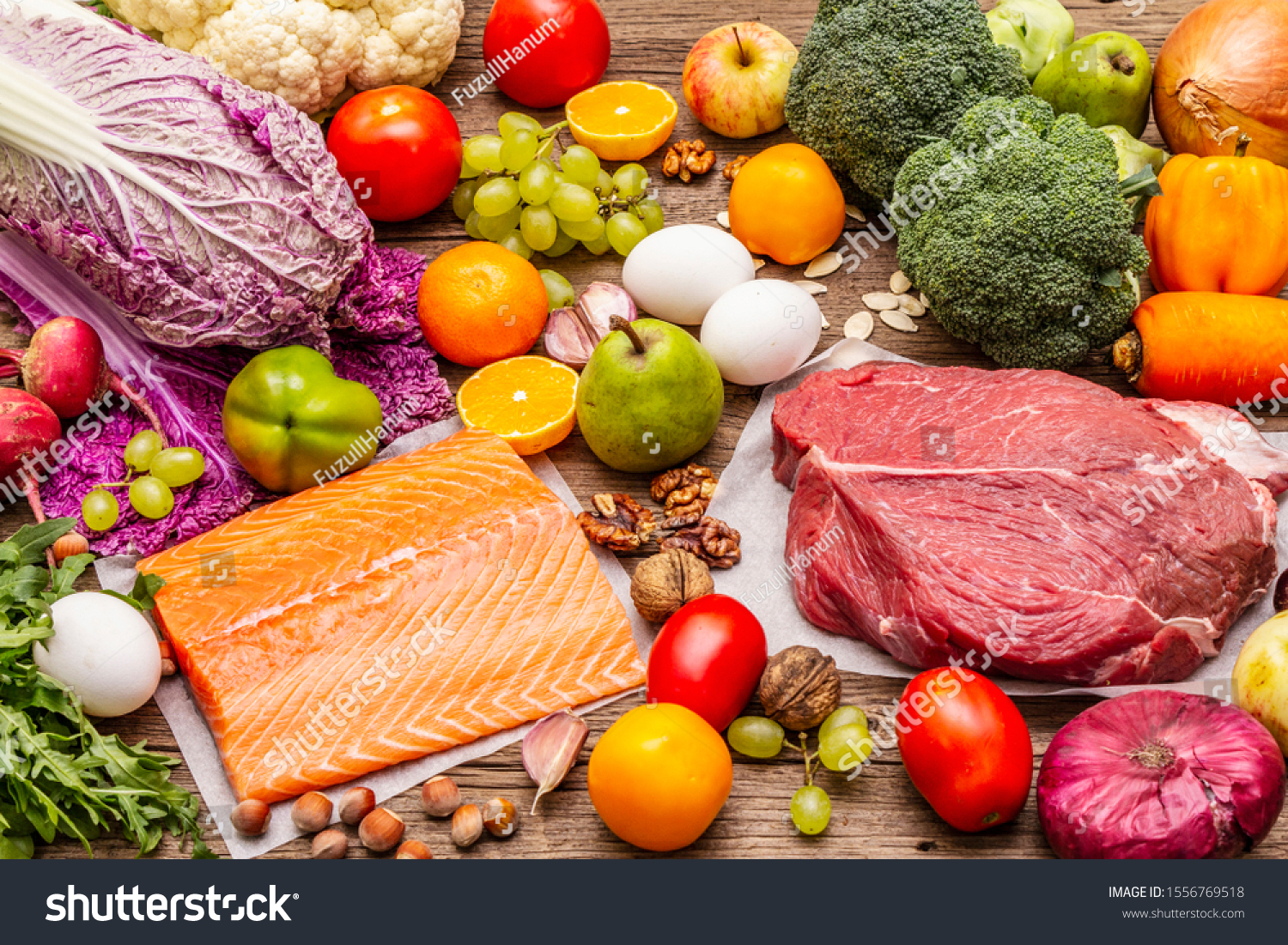 Trending paleo/pegan diet. Healthy balanced food concept. Set of fresh products, raw meat, salmon, vegetables and fruits. Old wooden boards background #1556769518