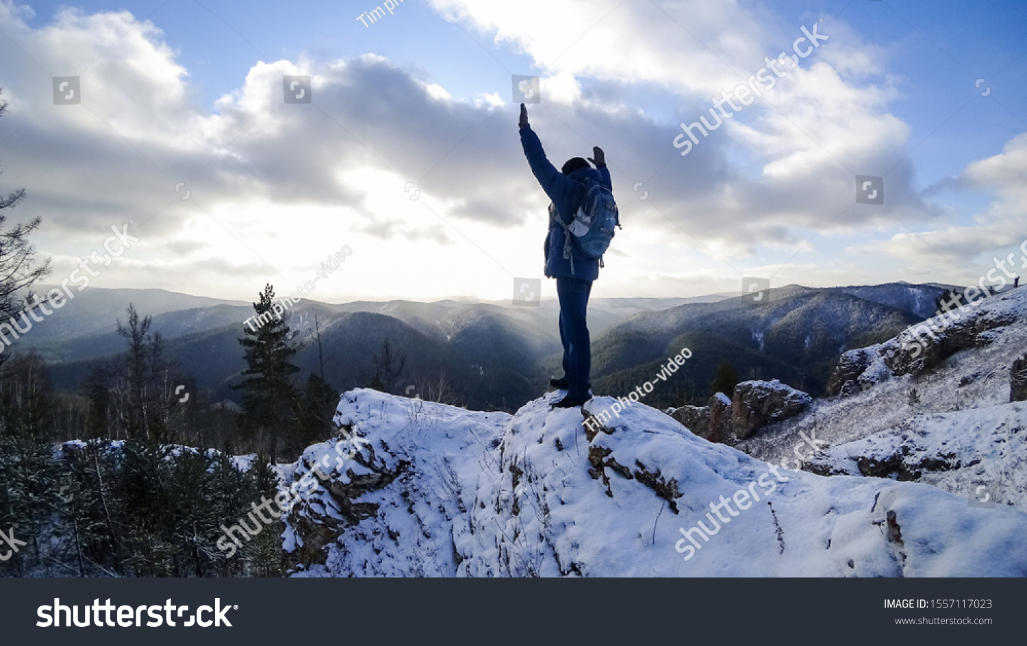 stock-photo-man-on-top-of-the-cliff-rais