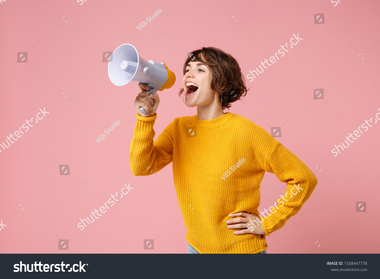 Funny young brunette woman girl in yellow sweater posing isolated on pastel pink wall background studio portrait. People sincere emotions lifestyle concept. Mock up copy space. Screaming in megaphone #1558447778