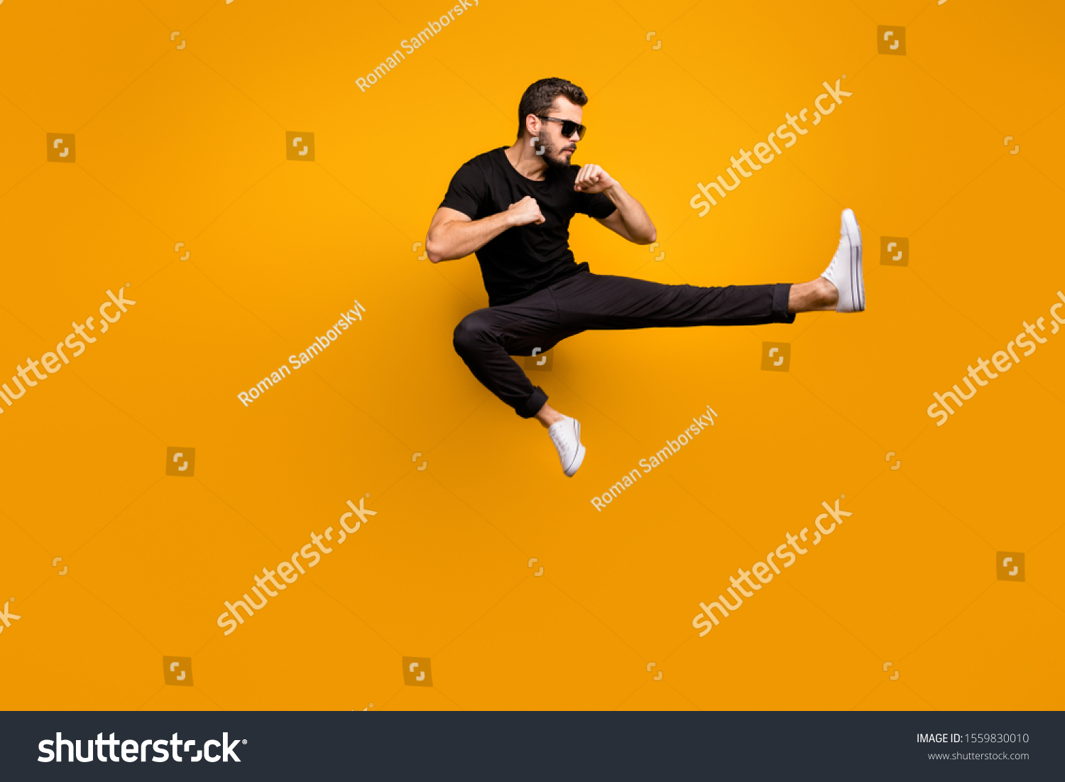Full length photo of handsome guy jumping high practicing self defense kicking confident facial expression wear sun specs black t-shirt pants isolated yellow color background #1559830010