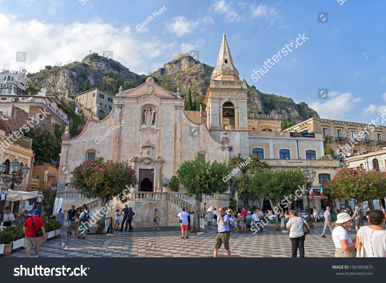 TAORMINA, SICILY, ITALY - SEPTEMBER 17, 2019: Tourists enjoy a late afternoon on Piazza IX Aprile (Square 9th of April) in front of the Church of San Giuseppe (St. Joseph) in Taormina, Sicily, Italy.