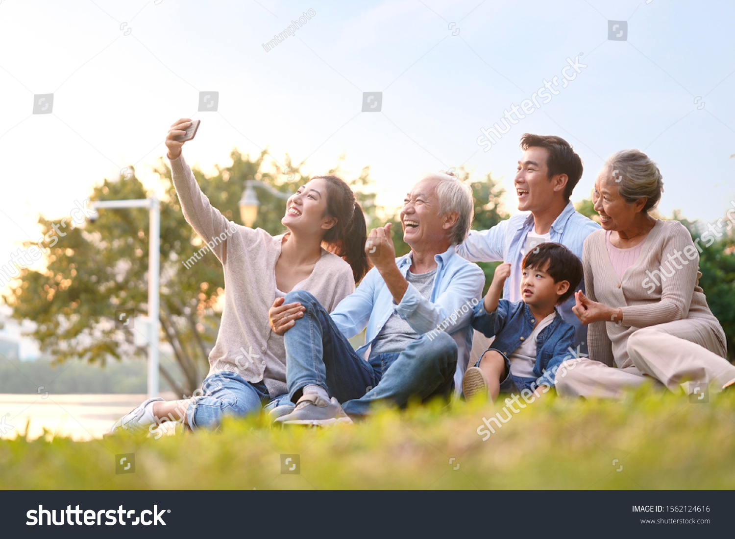 three generation happy asian family sitting on grass taking a selfie using mobile phone outdoors in park #1562124616