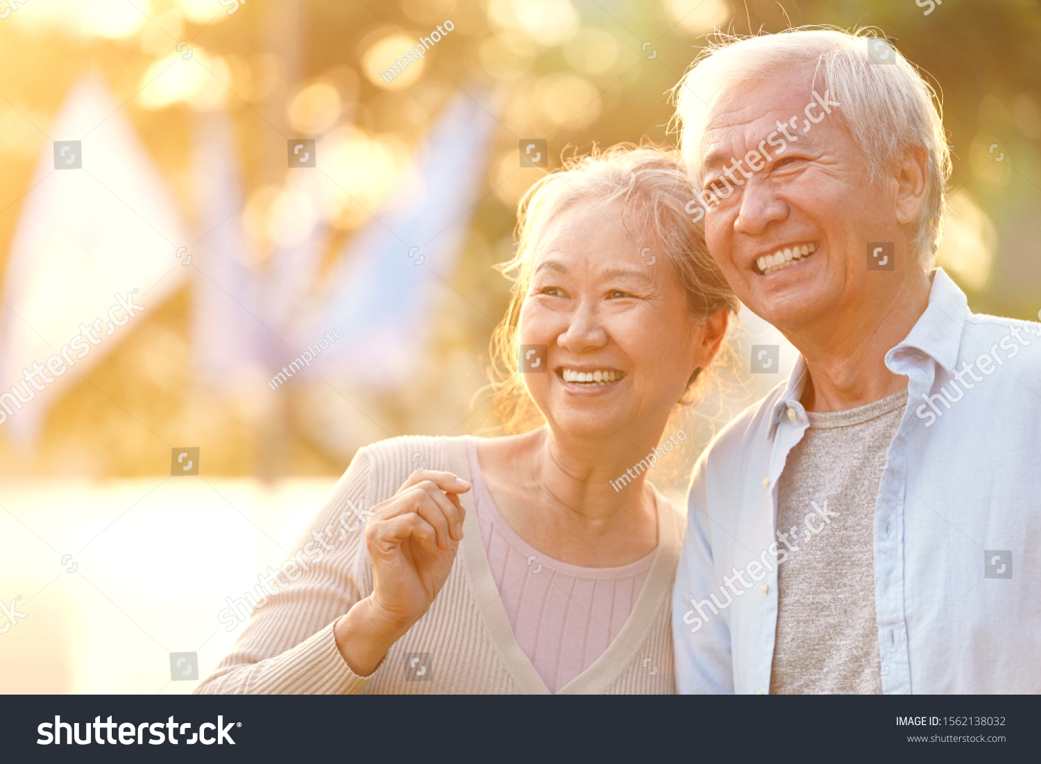 senior asian couple enjoying good time outdoors in park at dusk, happy and smiling #1562138032