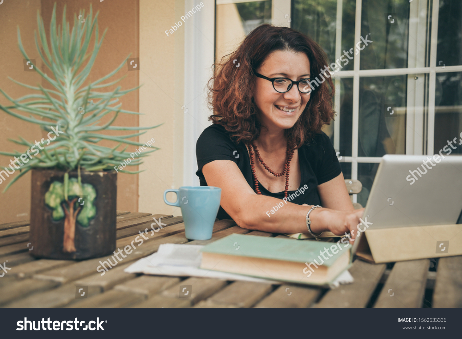 Middle aged female studying at home with books, newspaper and digital tablet pad. Woman reading a book and watching video online on new tech device. Education, modern lifestyle and leisure concept. #1562533336