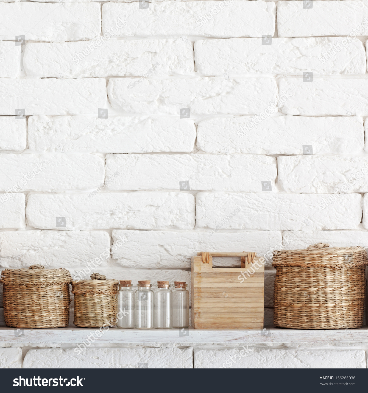 Plain wood table with hipster brick wall background stock photo - Decorative Shelf On White Brick Wall With Vintage Bottles And Wicker Jars On It