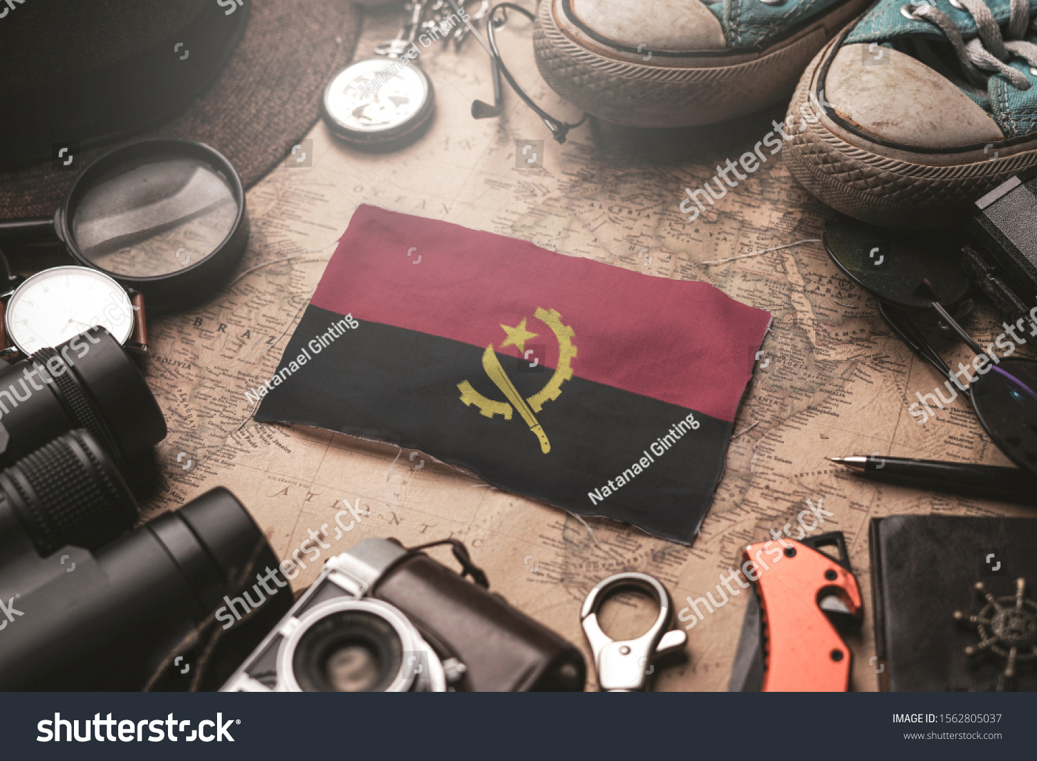 Angola Flag Between Traveler's Accessories on Old Vintage Map. Tourist Destination Concept. Tourist Destination Concept. #1562805037
