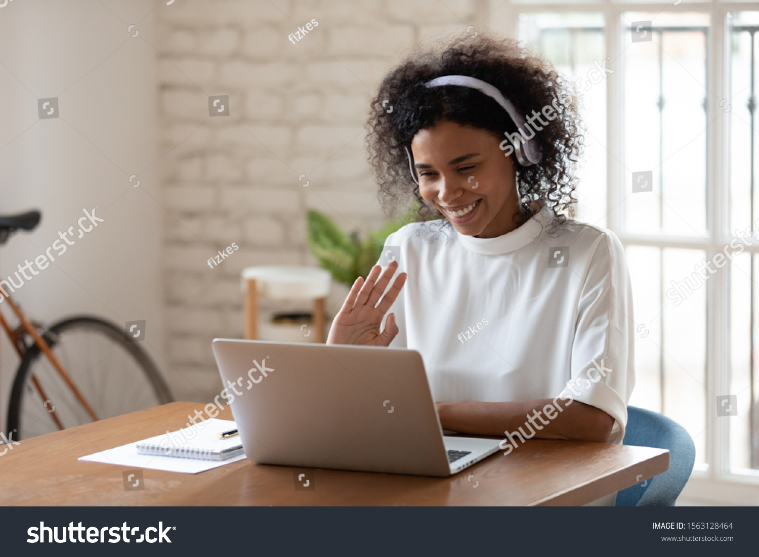 Happy african american young business woman wearing wireless headphones, looking at computer screen, waving hello. Pleasant attractive mixed race female professional holding video call with client. #1563128464