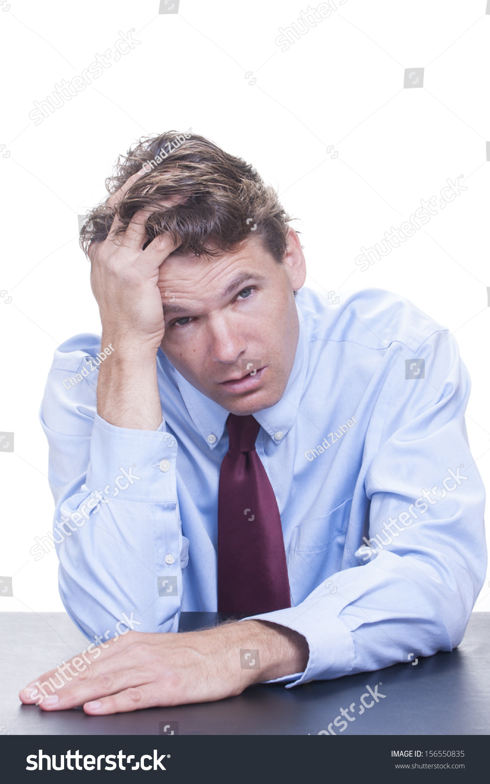 Frustrated office worker on the phone holding stock photo image - Frustrated White Male Office Worker Leans His Head Into His Hand As He Slouches At His