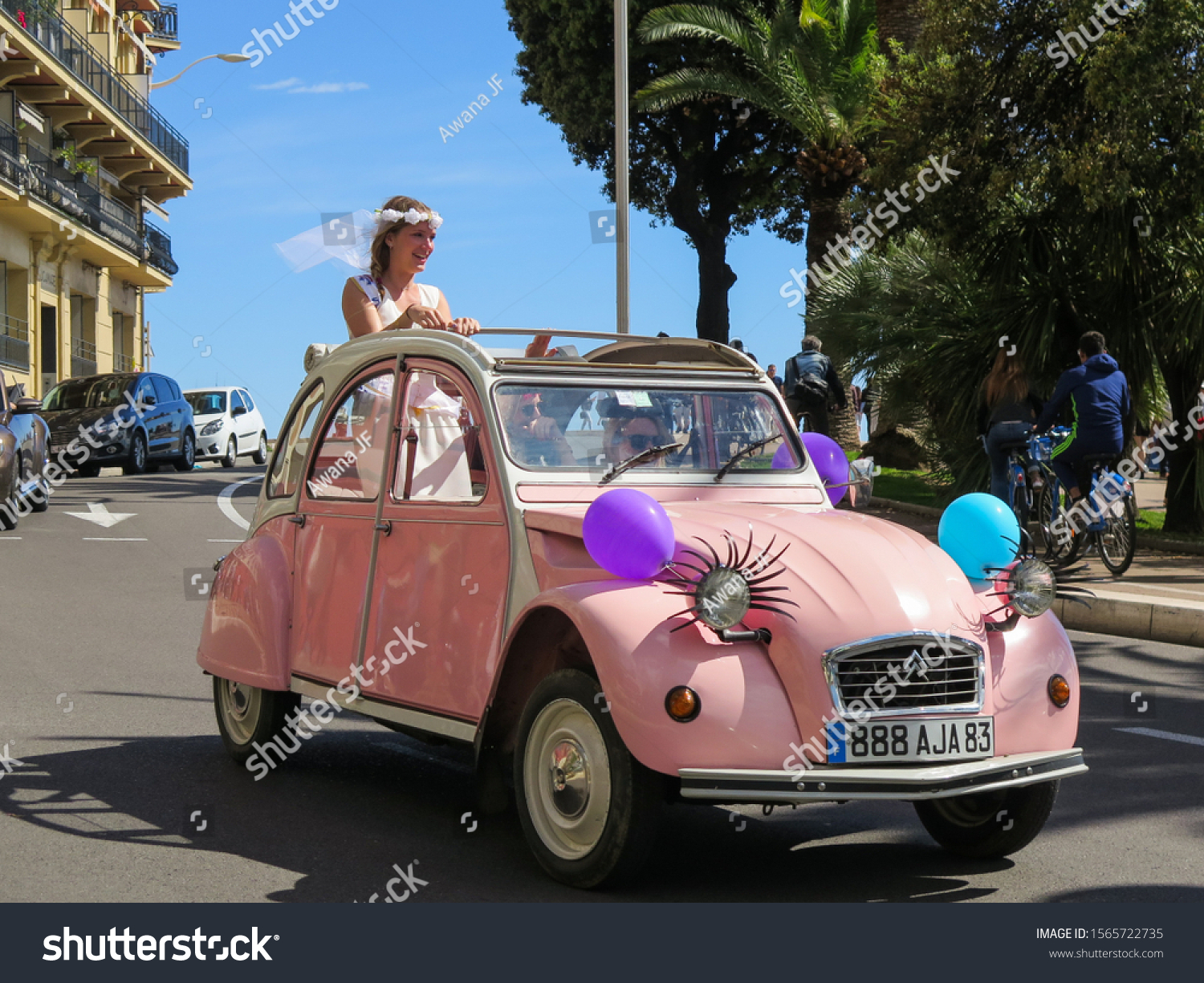 Nice, France - Mai 2017: Wedding bride ridding a pink old vintage car on a sunny day in the south of France