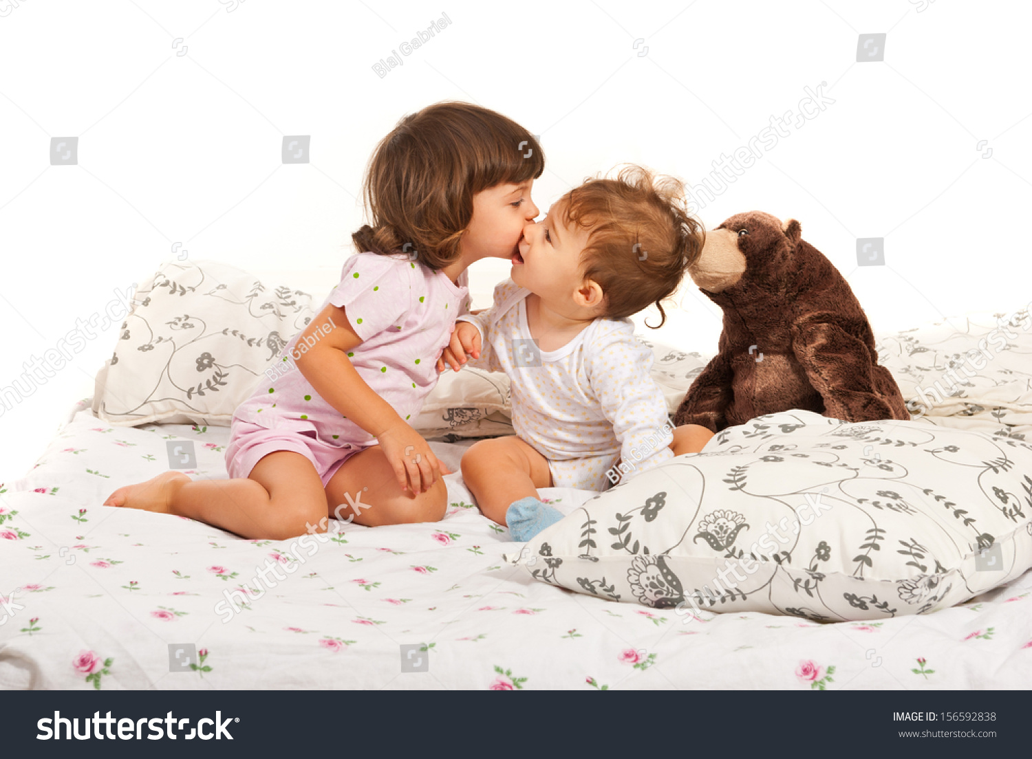 Toddler girl kissing baby boy sitting stock photo for Boys and girls in bed