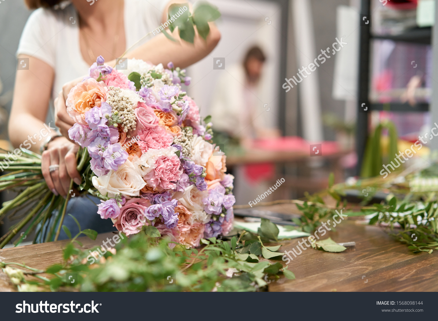 European floral shop concept. Florist woman creates beautiful bouquet of mixed flowers. Handsome fresh bunch. Education, master class and floristry courses. Flowers delivery. #1568098144