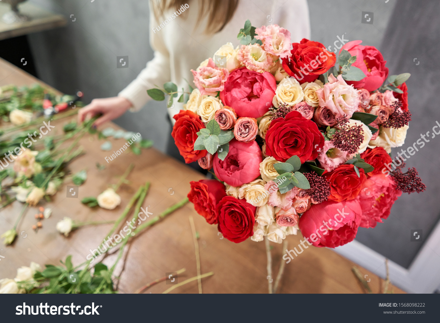European floral shop concept. Florist woman creates red beautiful bouquet of mixed flowers. Handsome fresh bunch. Education, master class and floristry courses. Flowers delivery. #1568098222
