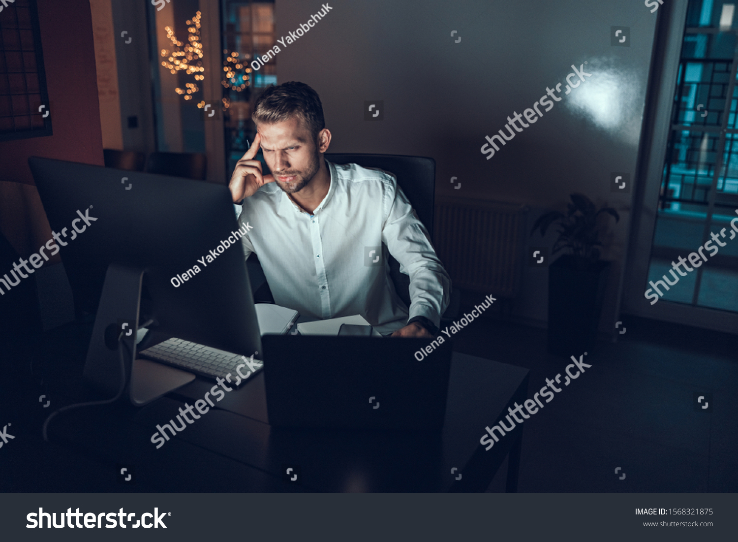 Serious male worker sitting at his workplace late at night #1568321875