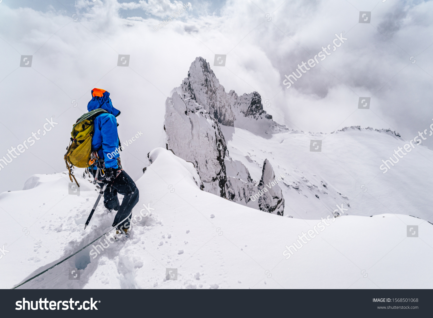 An alpinist climbing an alpine ridge in winter extreme conditions. Adventure ascent of alpine peak in snow and on rocks. Climber ascent to the summit. Winter ice and snow climbing in mountains. #1568501068