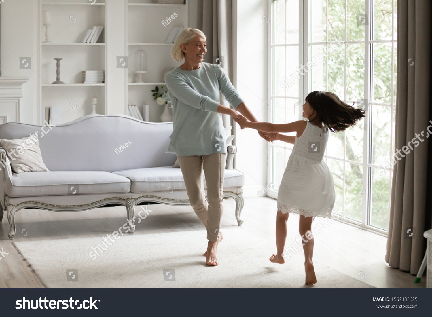 Healthy active 50s grandmother holding hands little granddaughter dancing or spinning standing barefoot in modern warm living room enjoy priceless time together at funny weekend activities concept #1569483625