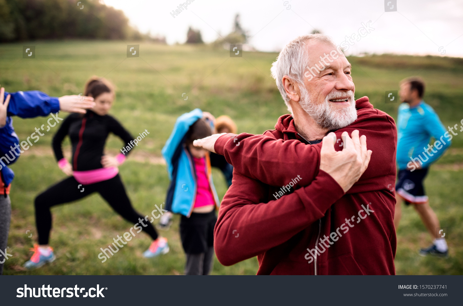 Large group of fit and active people doing exercise in nature, stretching. #1570237741