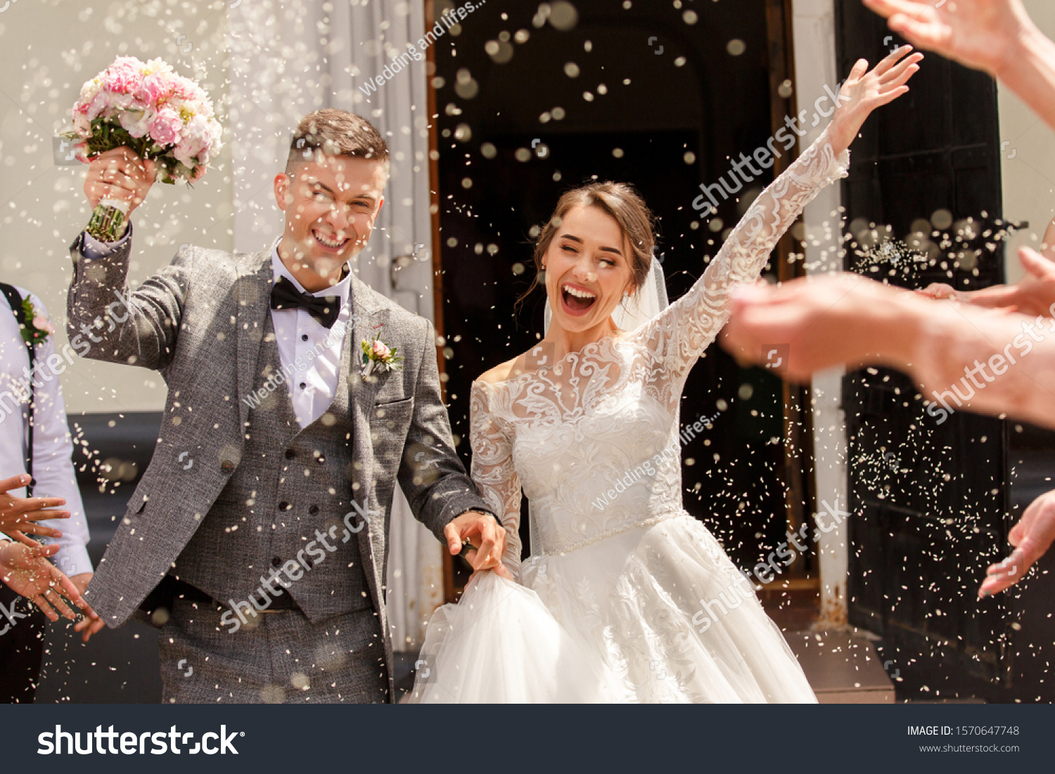 Happy wedding photography of bride and groom at wedding ceremony. Wedding tradition sprinkled with rice and grain #1570647748