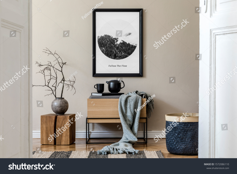 Modern scandinavian living room interior with black mock up poster frame, design commode,  leaf in vase, black rattan basket, books and elegant accessories. Template. Stylish home decor.  #1572086110