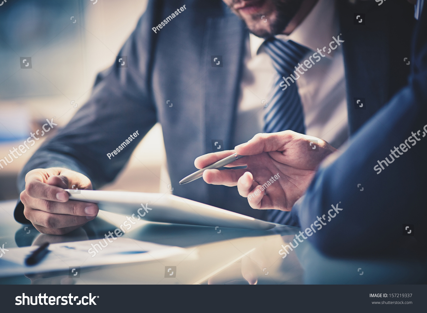 Image of two young businessmen using touchpad at meeting #157219337 - 123PhotoFree.com