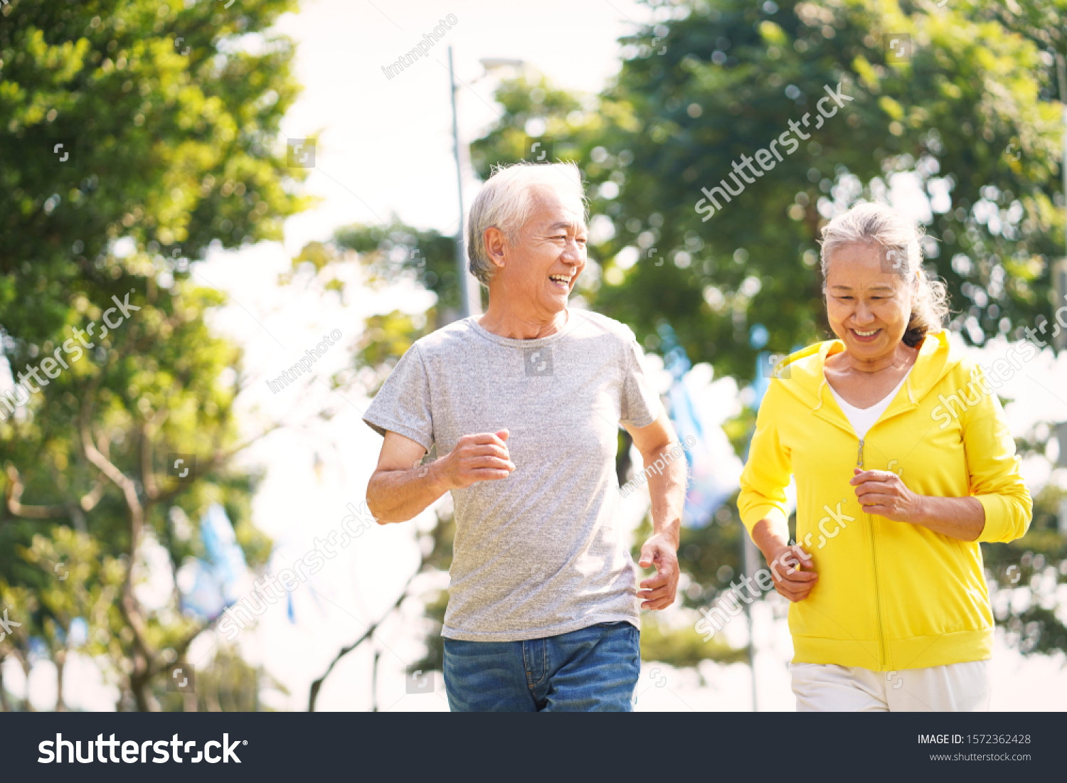 happy asian senior couple running exercising outdoors in park #1572362428