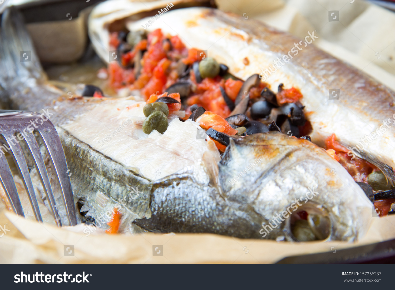 Baked whole white fish, sea bass stuffed with black olives, capers and ...