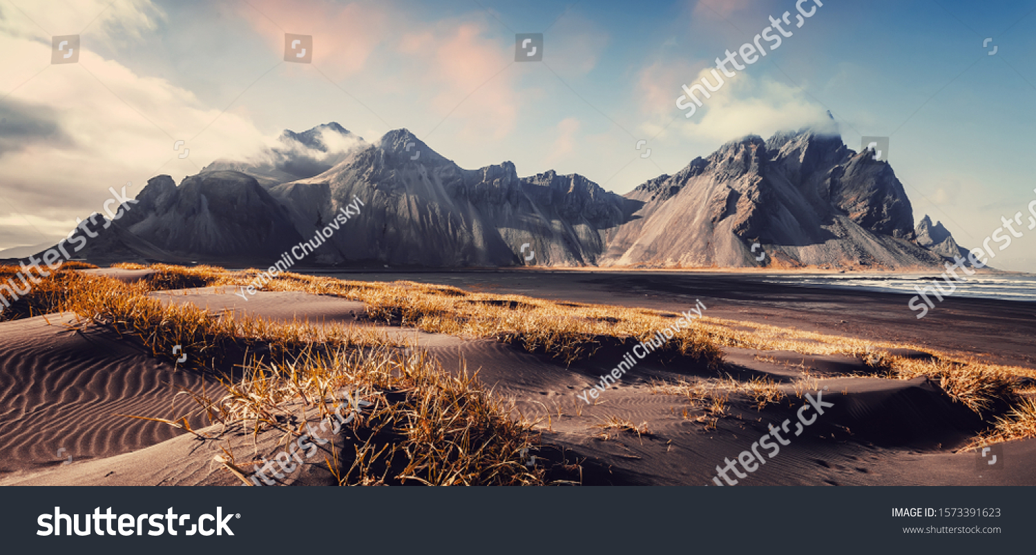 Vestrahorn mountaine on Stokksnes cape in Iceland during sunset. Amazing Iceland nature seascape. popular tourist attraction. Best famouse travel locations. Scenic Image of Iceland #1573391623