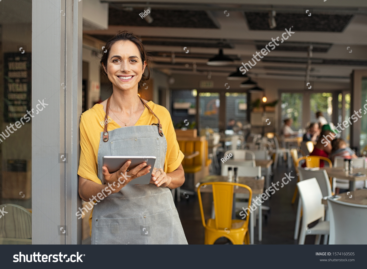 Portrait of happy woman standing at doorway of her store. Cheerful mature waitress waiting for clients at coffee shop. Successful small business owner in casual wearing grey apron standing at entrance #1574160505