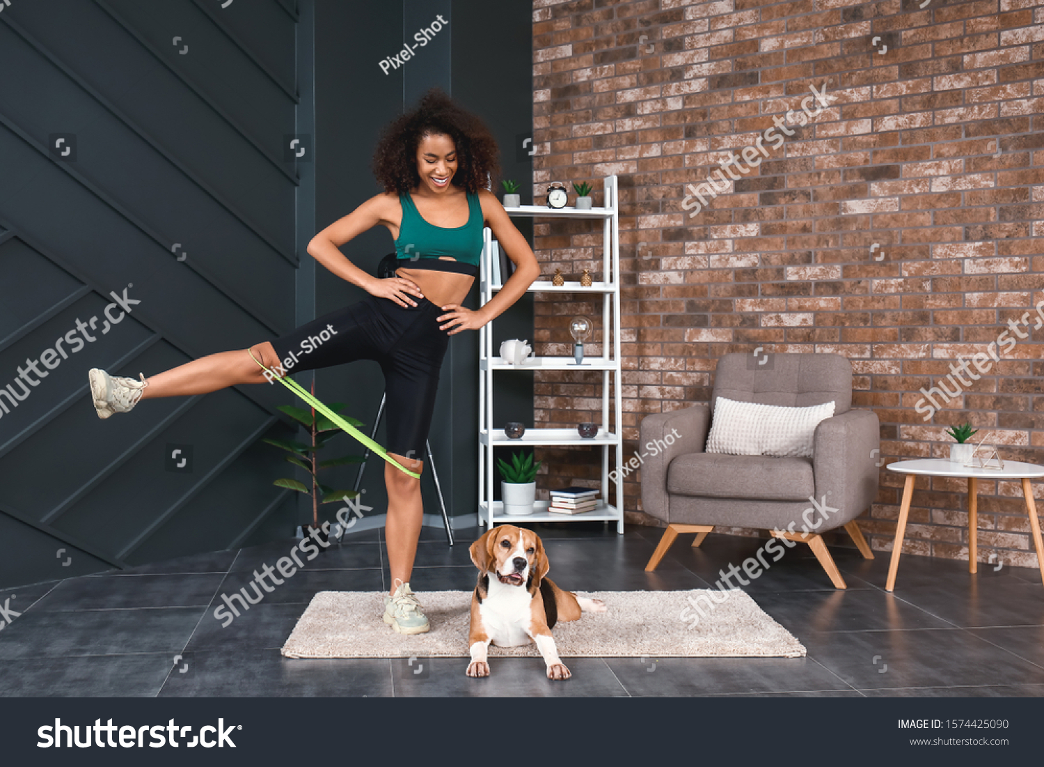 Sporty African-American woman with cute dog training at home #1574425090