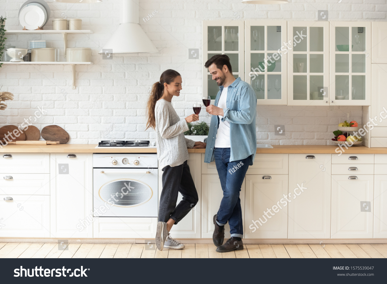 Romantic affectionate beautiful young couple holding glasses standing in modern cozy white kitchen room interior, happy married guy husband and girl wife drinking red wine celebrate together at home #1575539047