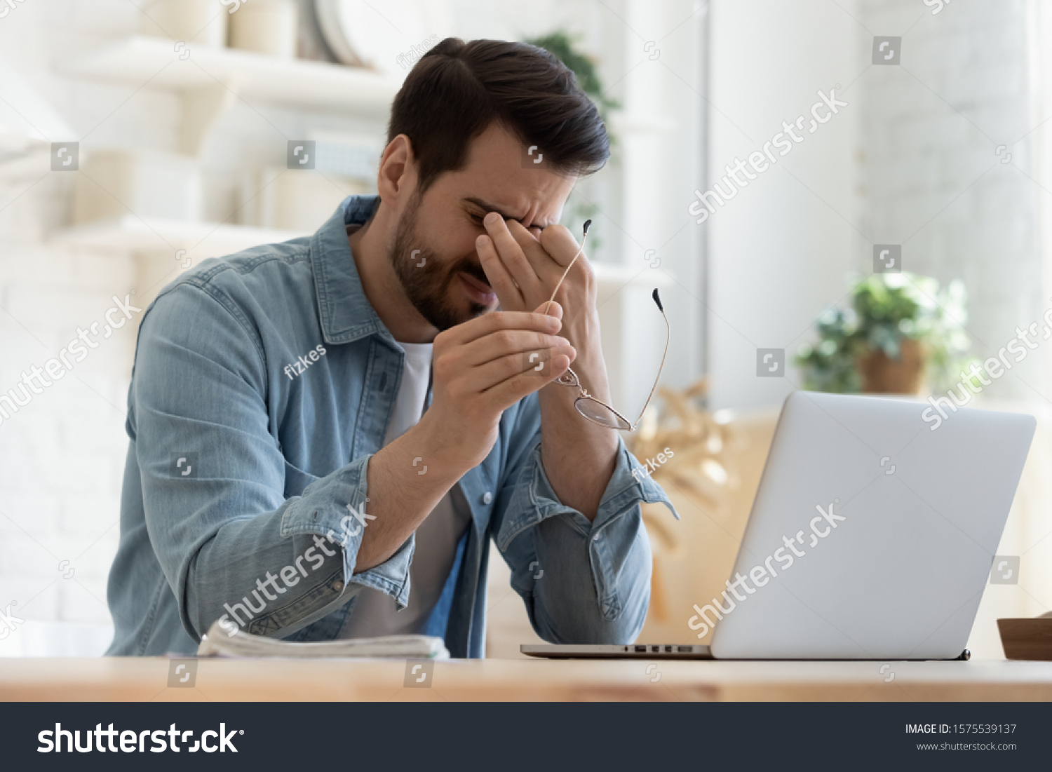 Tired young man feel pain eyestrain holding glasses rubbing dry irritated eyes fatigued from computer work, stressed man suffer from headache bad vision sight problem sit at home table using laptop #1575539137